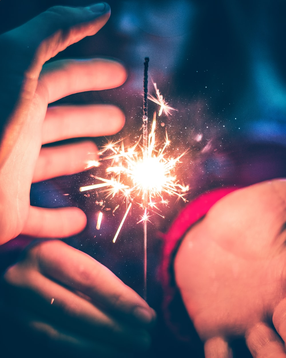 person holding white and red sparkler