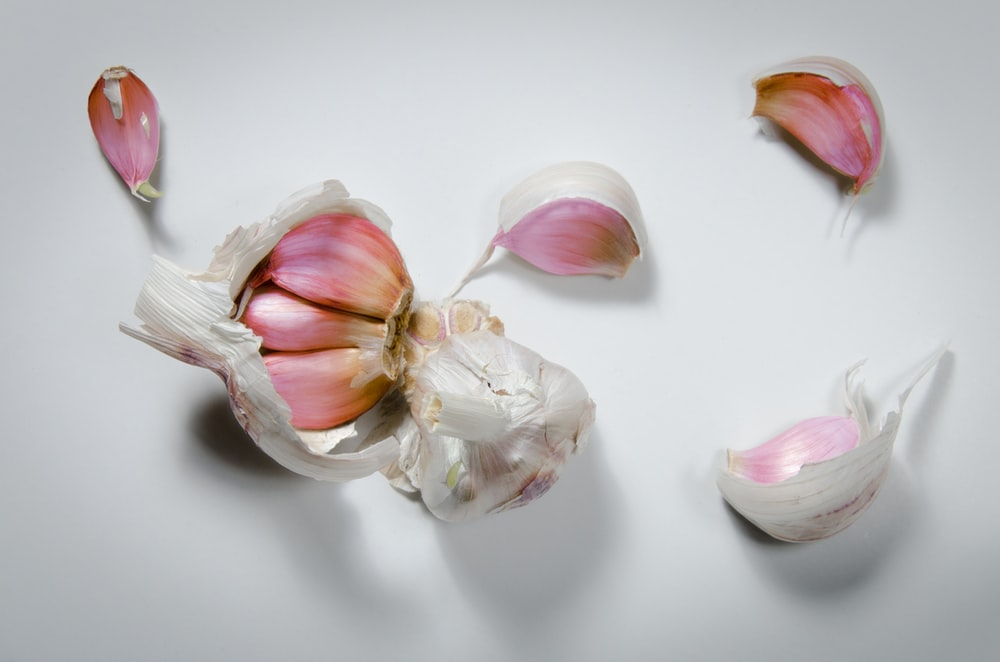 white and pink garlic on white surface