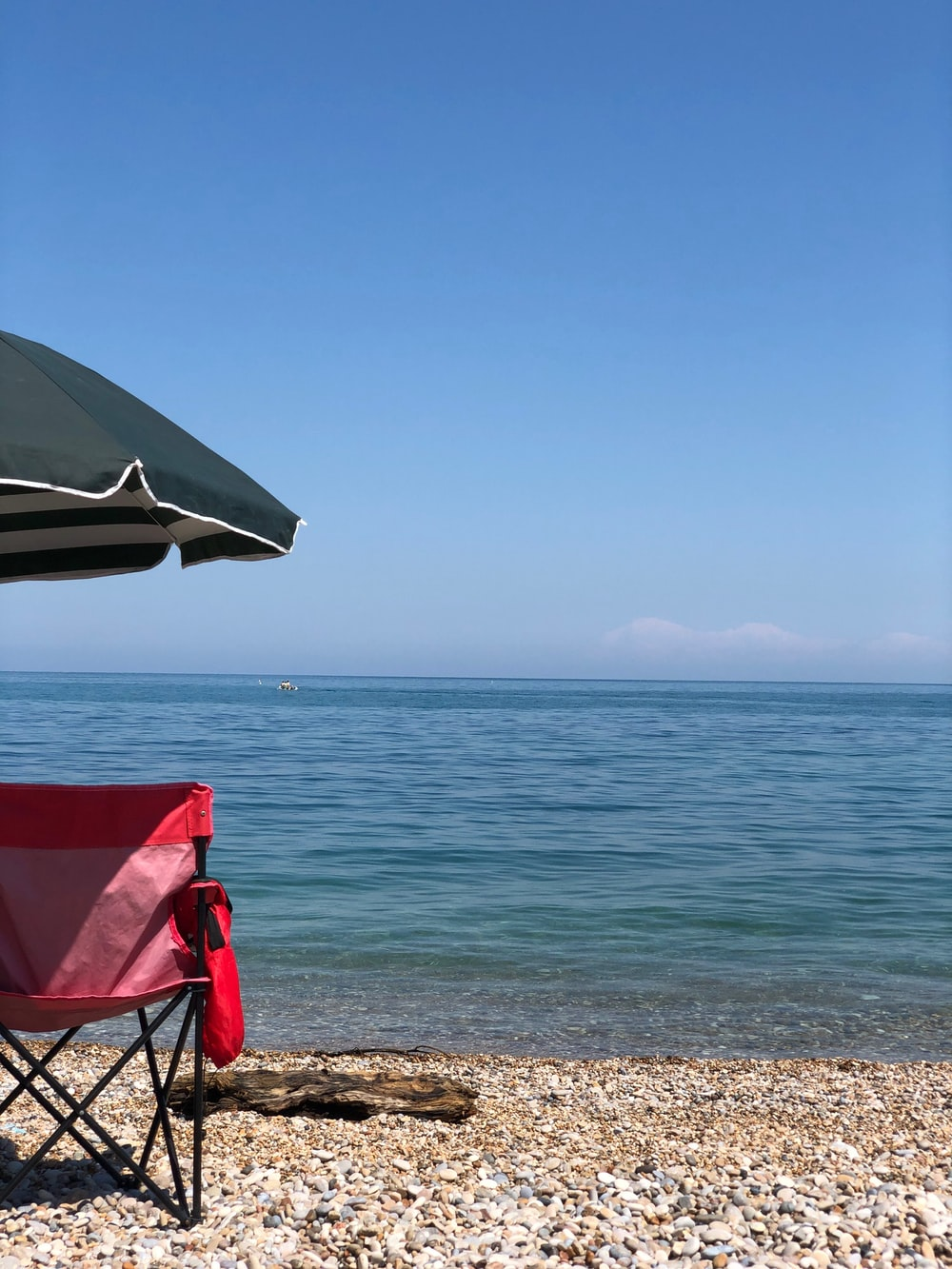 red and white folding chair on beach during daytime