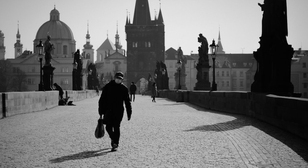 man in black jacket and pants walking on sidewalk in grayscale photography