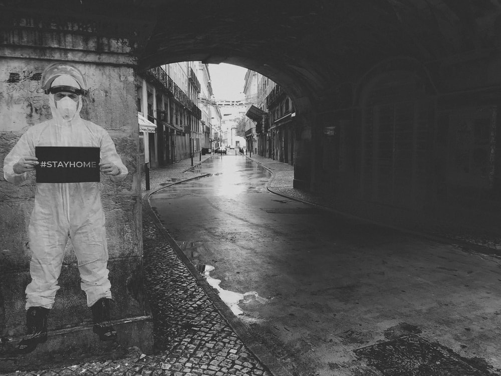 grayscale photo of man walking on tunnel