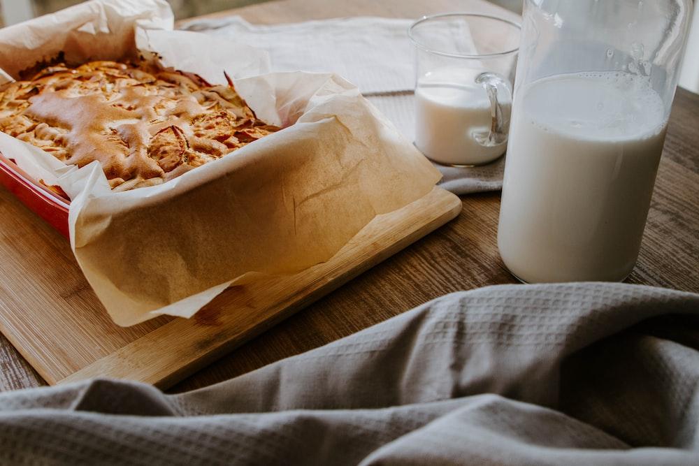 white ceramic mug beside brown bread on brown wooden tray