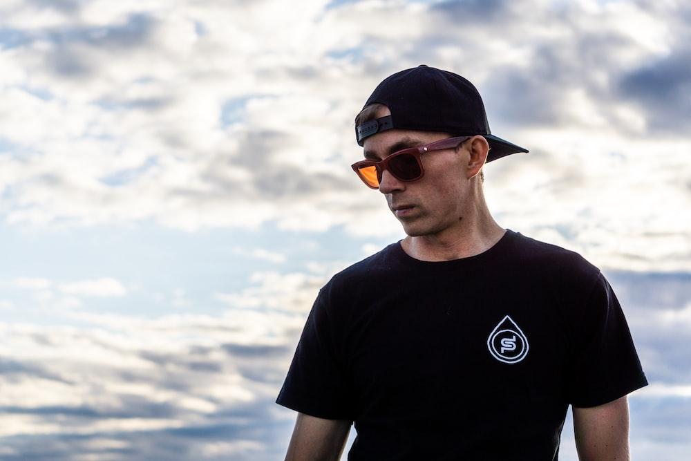 man in black crew neck t-shirt wearing orange sunglasses and black cap
