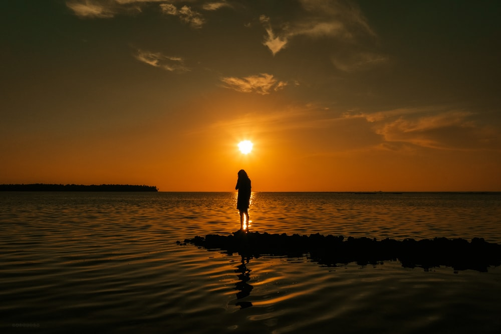 silhouette of woman walking on beach during sunset