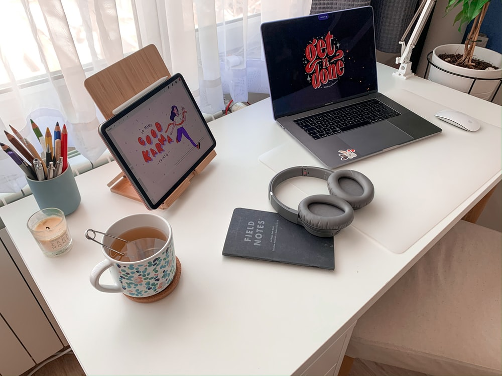 white and blue ceramic mug beside black and silver laptop computer on white table