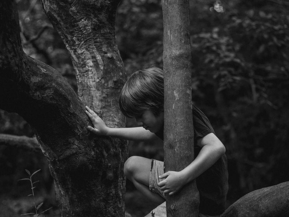 grayscale photo of woman climbing on tree