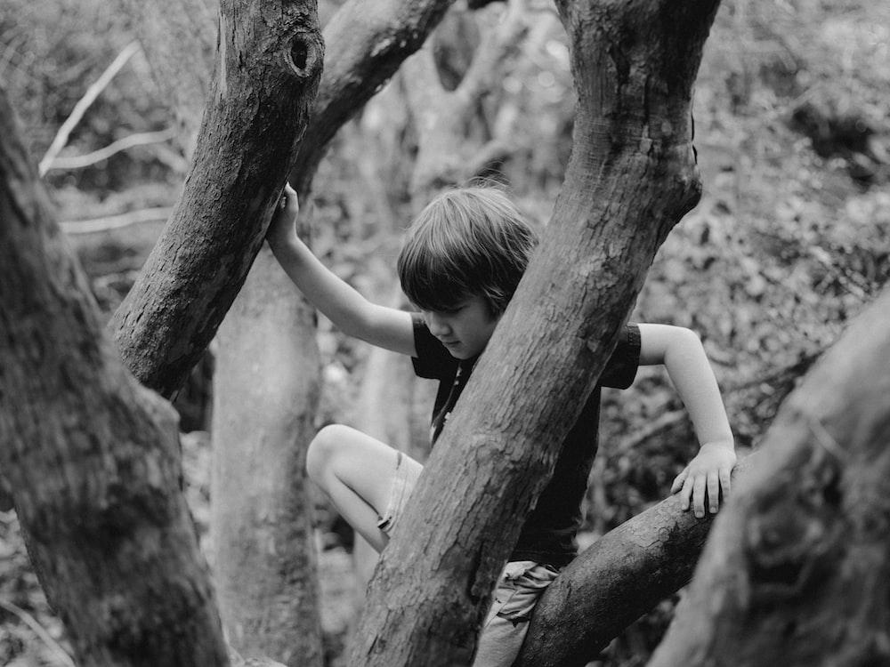 grayscale photo of woman in black tank top climbing on tree