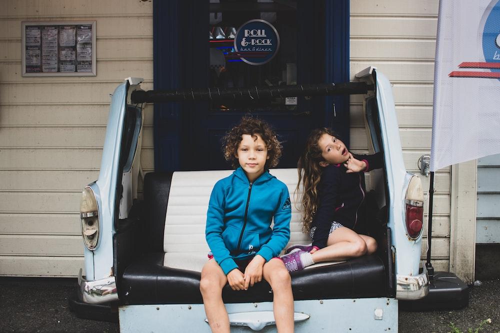 2 women sitting on car