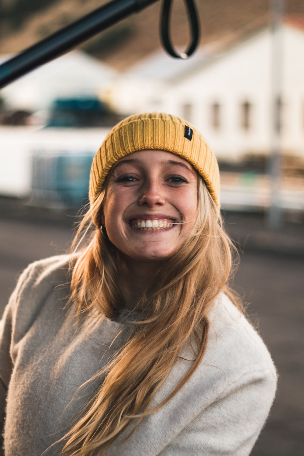 smiling woman in brown knit cap and gray sweater