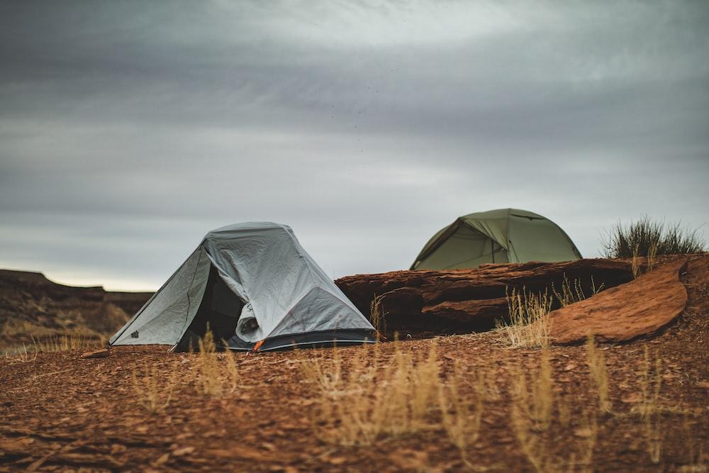 gray tent on brown grass field under gray sky