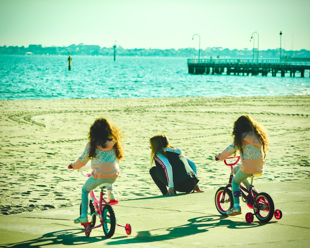 2 girls riding on bicycle on beach during daytime