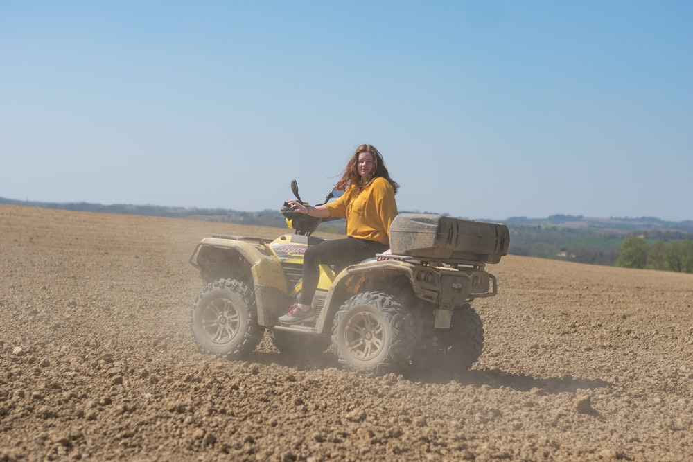 woman in brown jacket riding atv on brown field during daytime