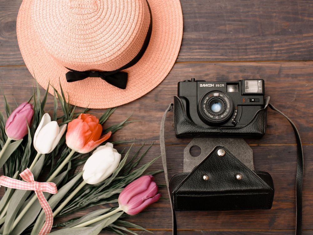 black and silver camera beside brown hat
