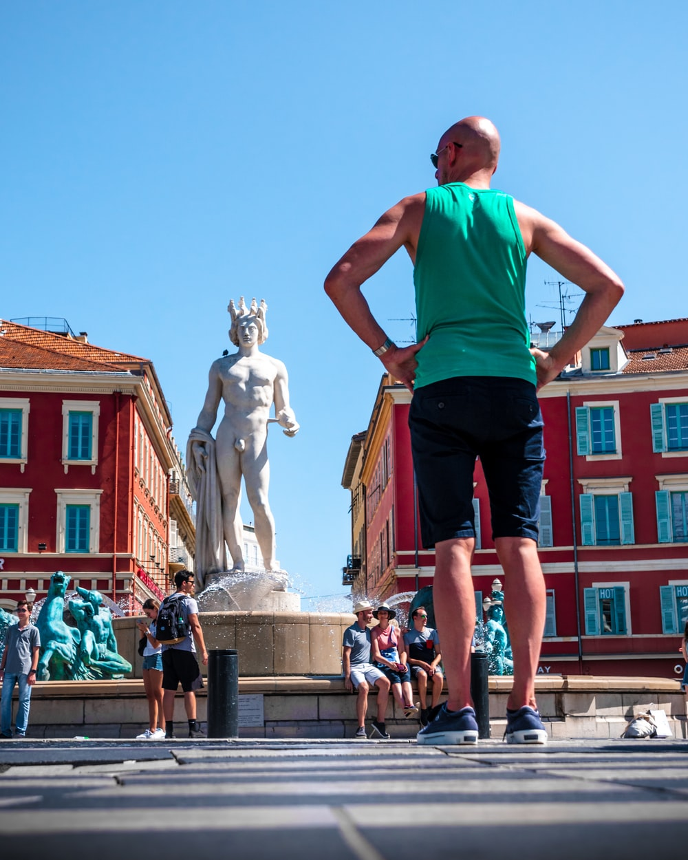 man in teal tank top and black shorts standing in front of statue