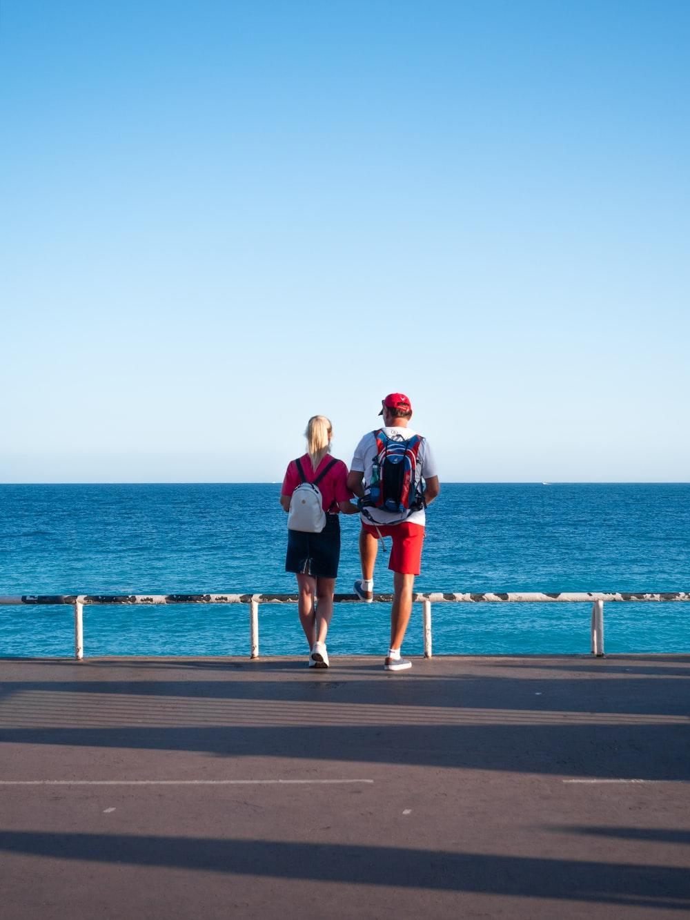2 men standing on dock near body of water during daytime