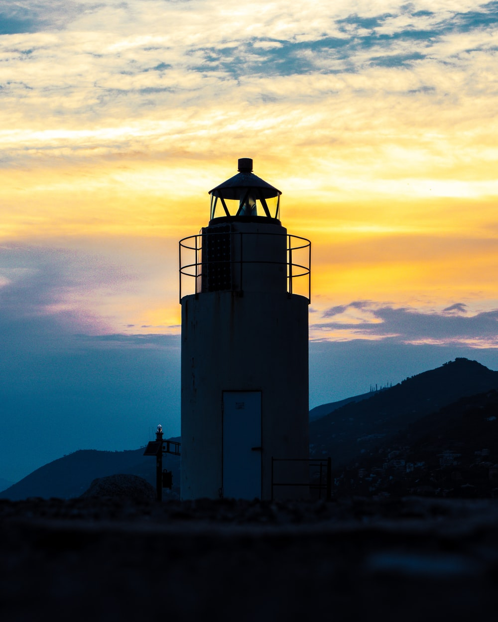 white and black lighthouse during sunset