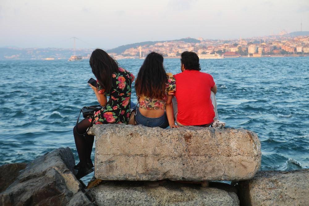 2 women sitting on rock near body of water during daytime
