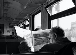 grayscale photo of man in black shirt sitting on train
