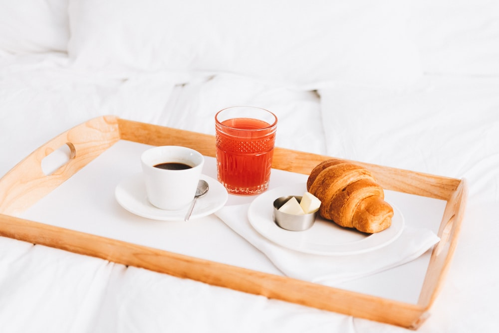 two brown breads on white ceramic plate beside white ceramic teacup on white table cloth