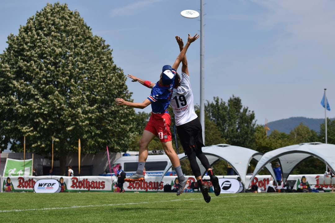 Ultimate Frisbee players jumping to reach the disc in the air.