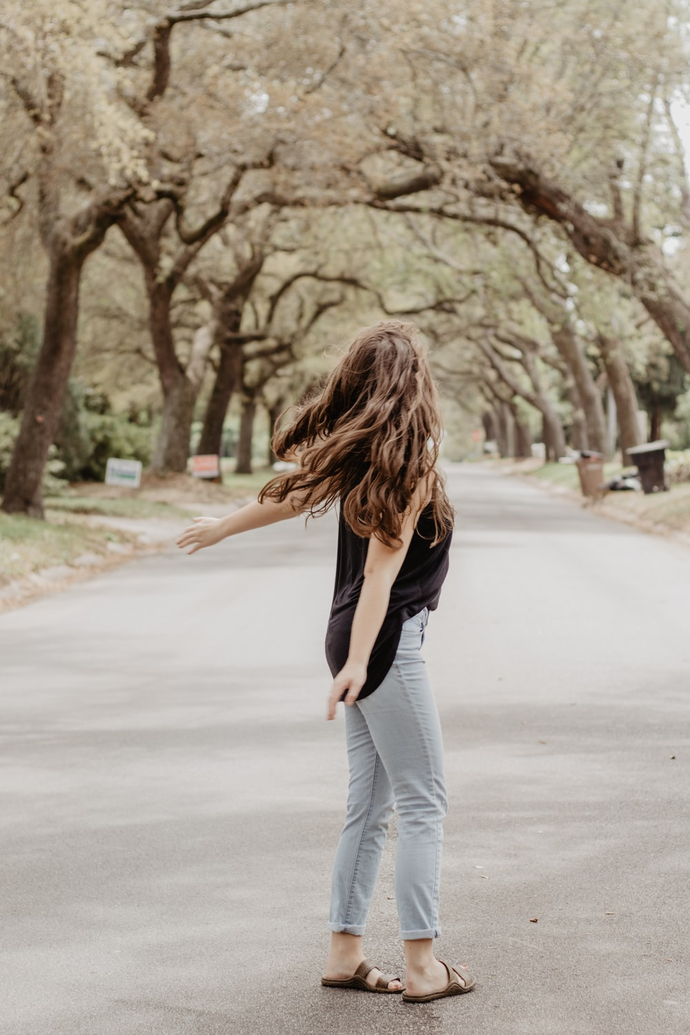 woman in black shirt and blue denim jeans standing on gray asphalt road during daytime