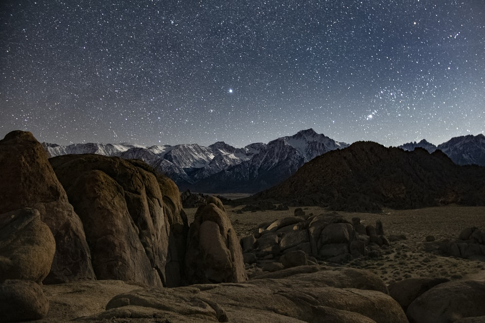 brown rocky mountain under blue sky during night time