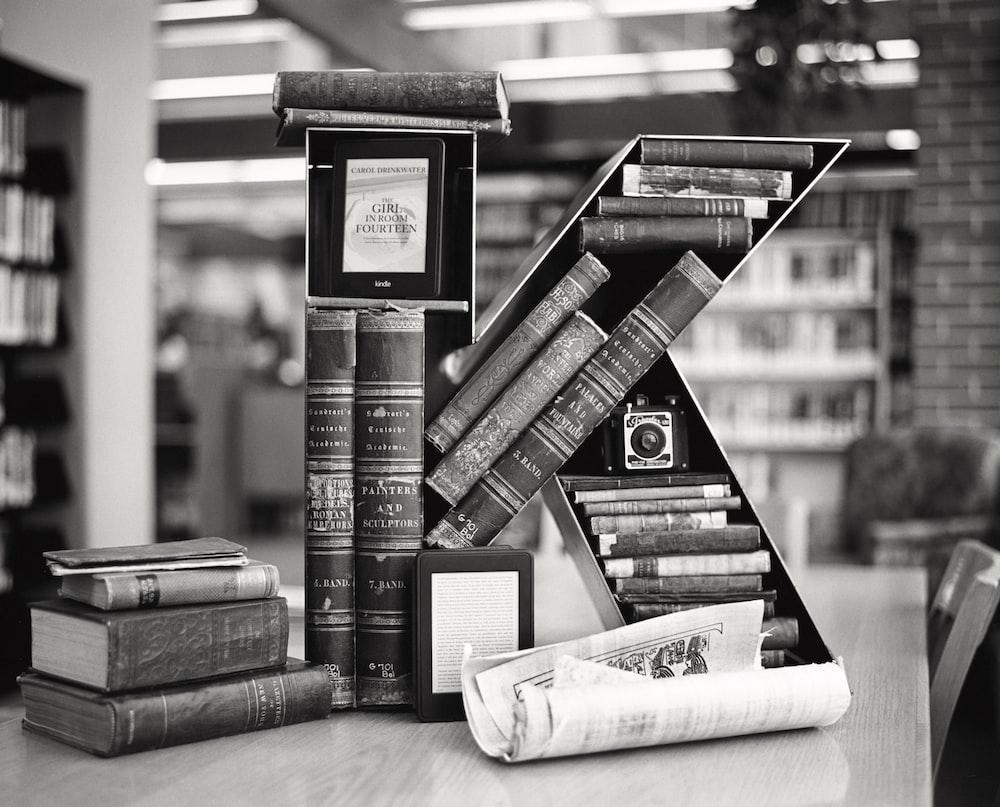 grayscale photo of books on shelf