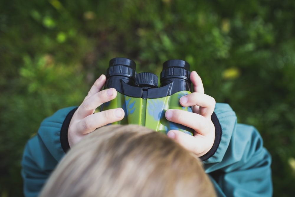 boy in green shirt holding binoculars