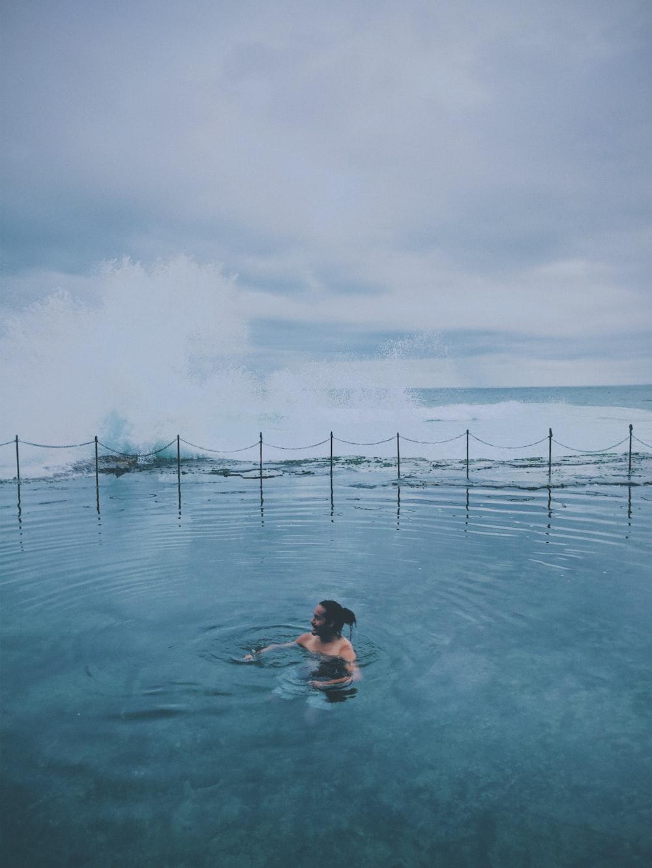 woman in blue bikini swimming on water