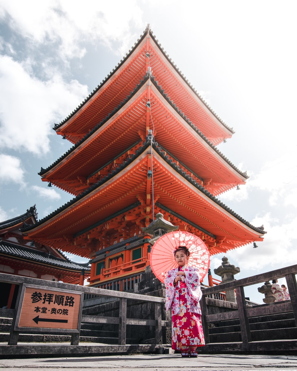 woman in pink and white floral dress standing near brown and white temple during daytime