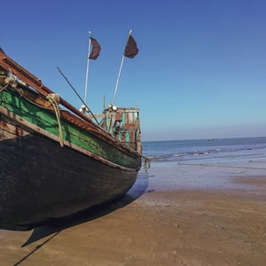 green and brown boat on beach during daytime