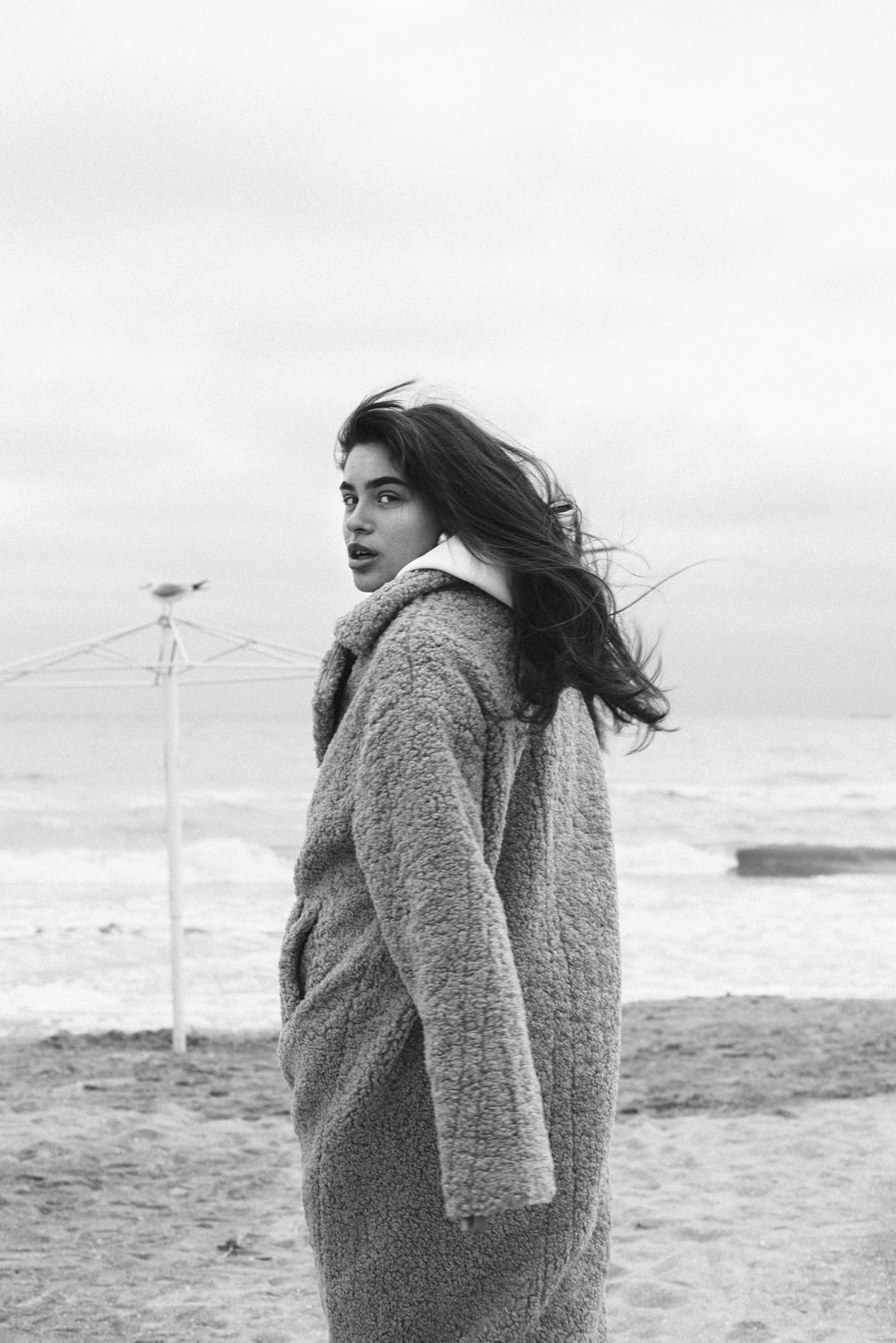 grayscale photo of woman in sweater standing on beach
