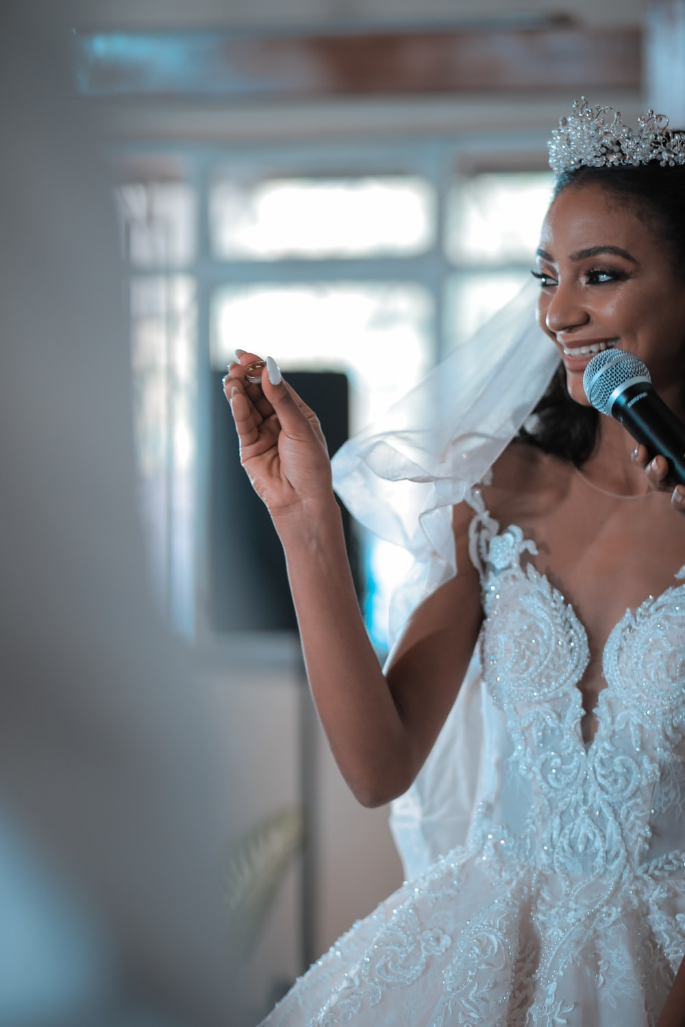 woman in white lace floral dress holding microphone