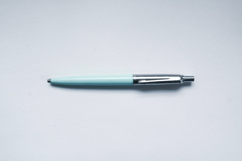 green and silver click pen