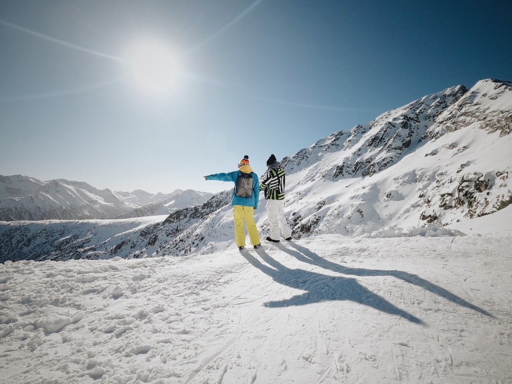woman in blue jacket and yellow pants standing on snow covered ground during daytime