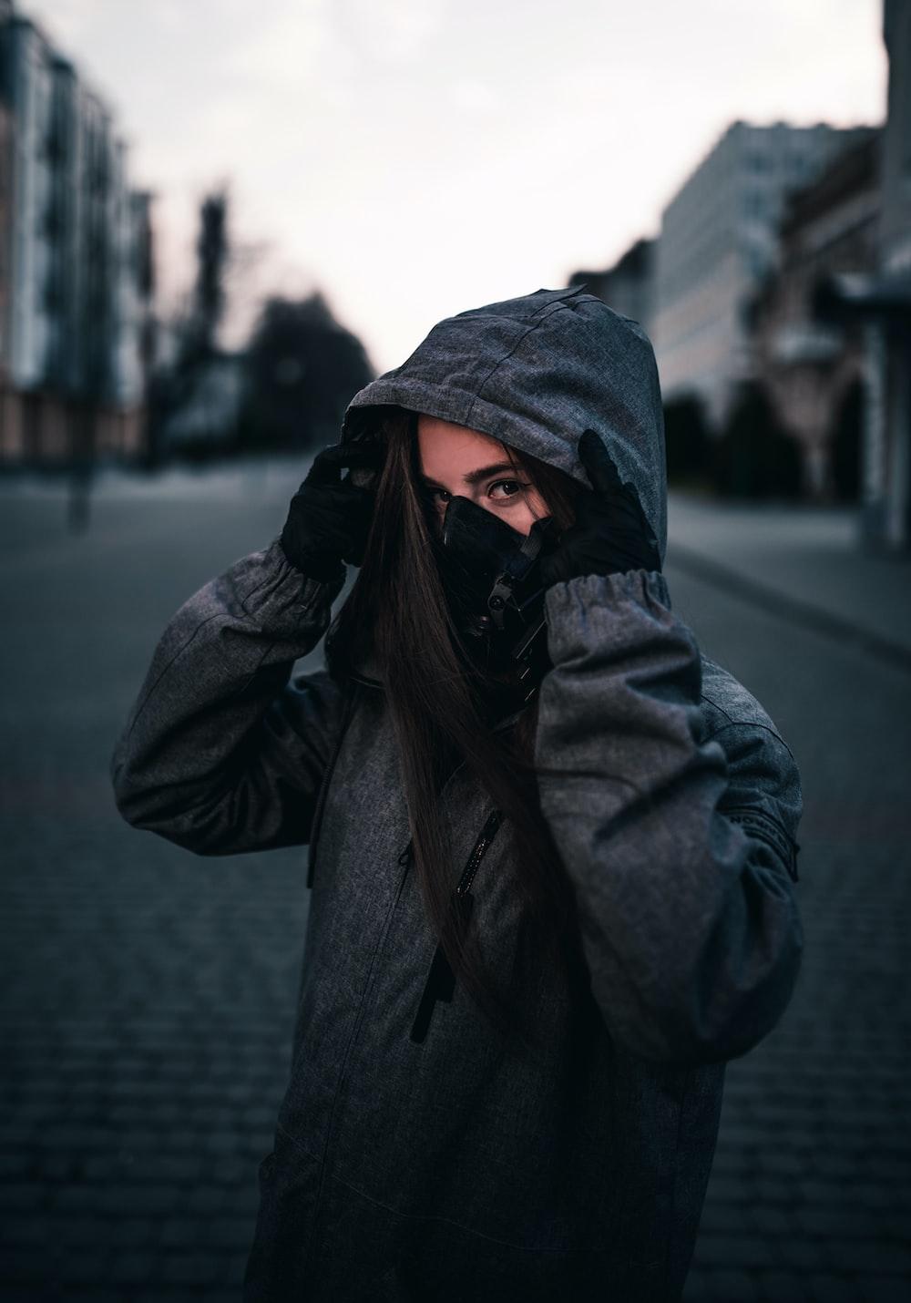 person in black hoodie standing on sidewalk during daytime