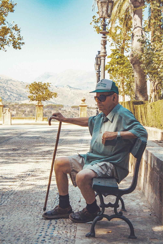 man in blue dress shirt sitting on brown wooden armchair