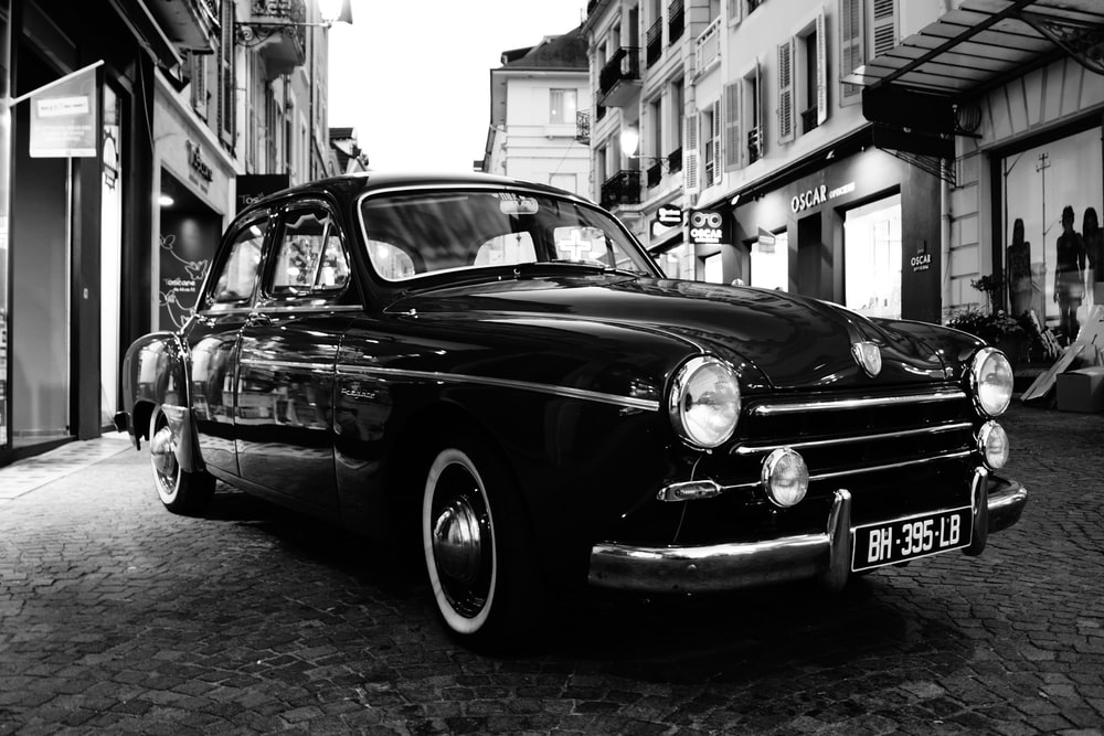 grayscale photo of classic car parked on street
