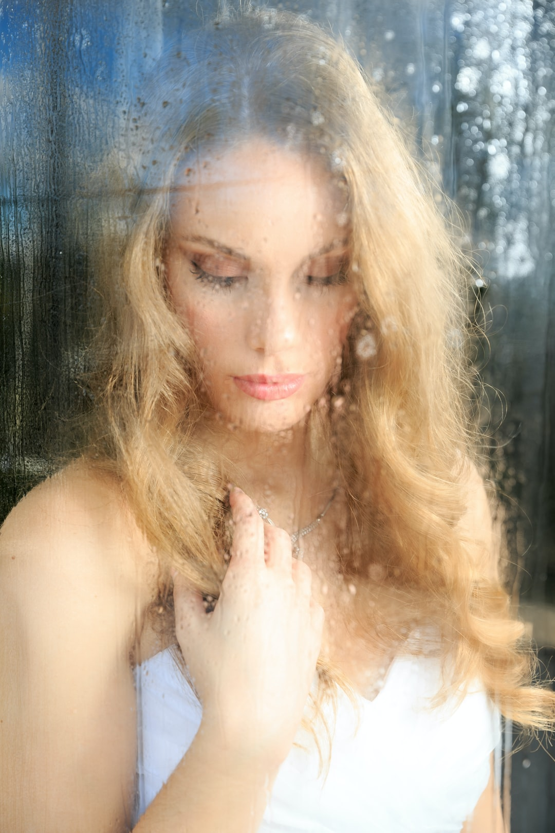 Thoughtful young woman behind a wet window glass