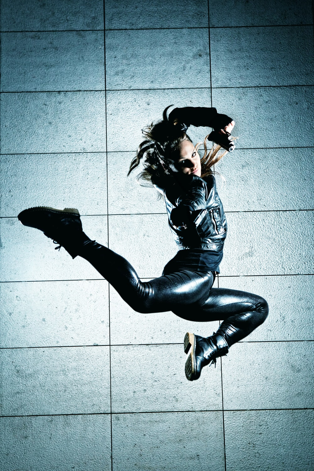 woman in black leather jacket and black pants lying on floor