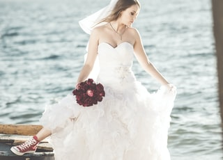 woman in white tube dress holding red rose bouquet