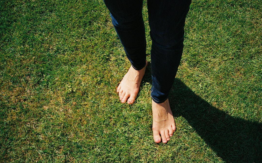 person in blue denim jeans standing on green grass field