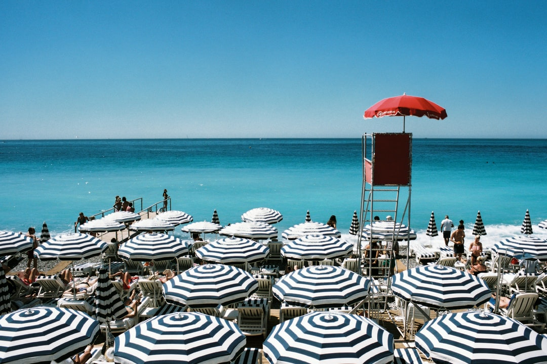 A private beach in Nice, France. Blue and white striped beach umbrellas and a red lifeguard seat. Shot on film.
