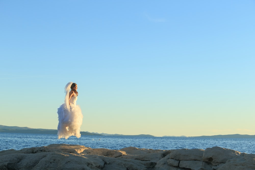 woman in white dress sitting on rock formation during daytime