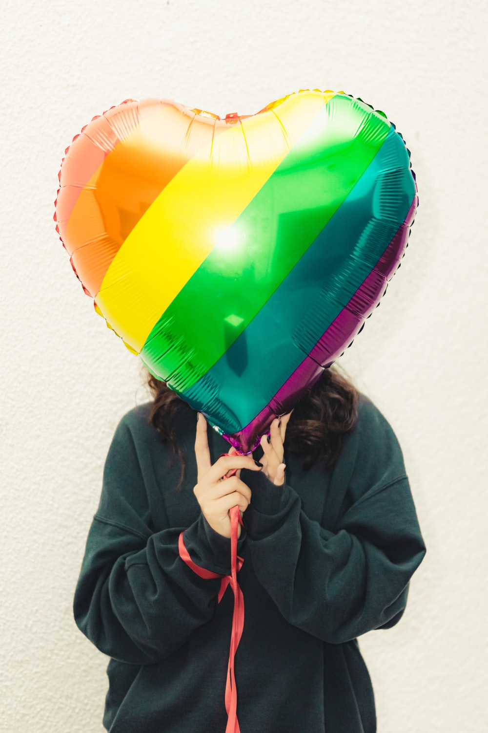 person holding yellow and green balloon