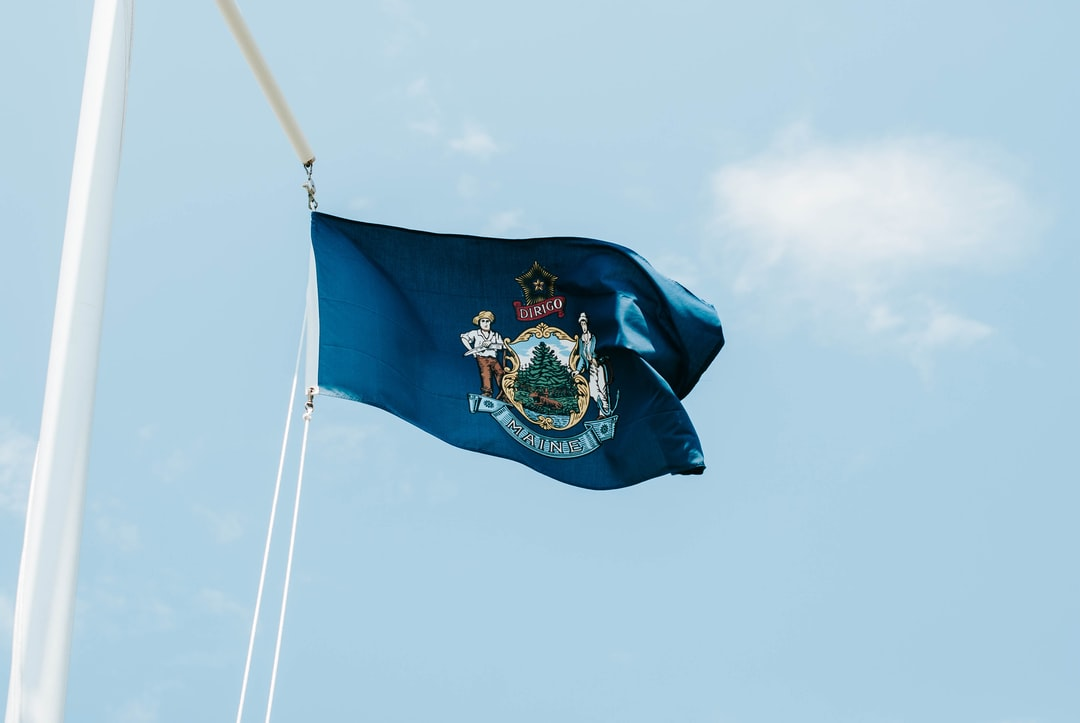 The Maine state flag flies at a lighthouse.