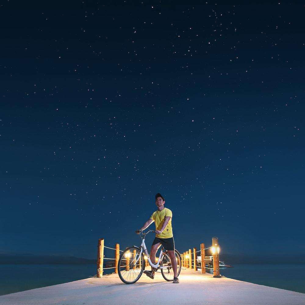 man in yellow shirt riding bicycle during night time