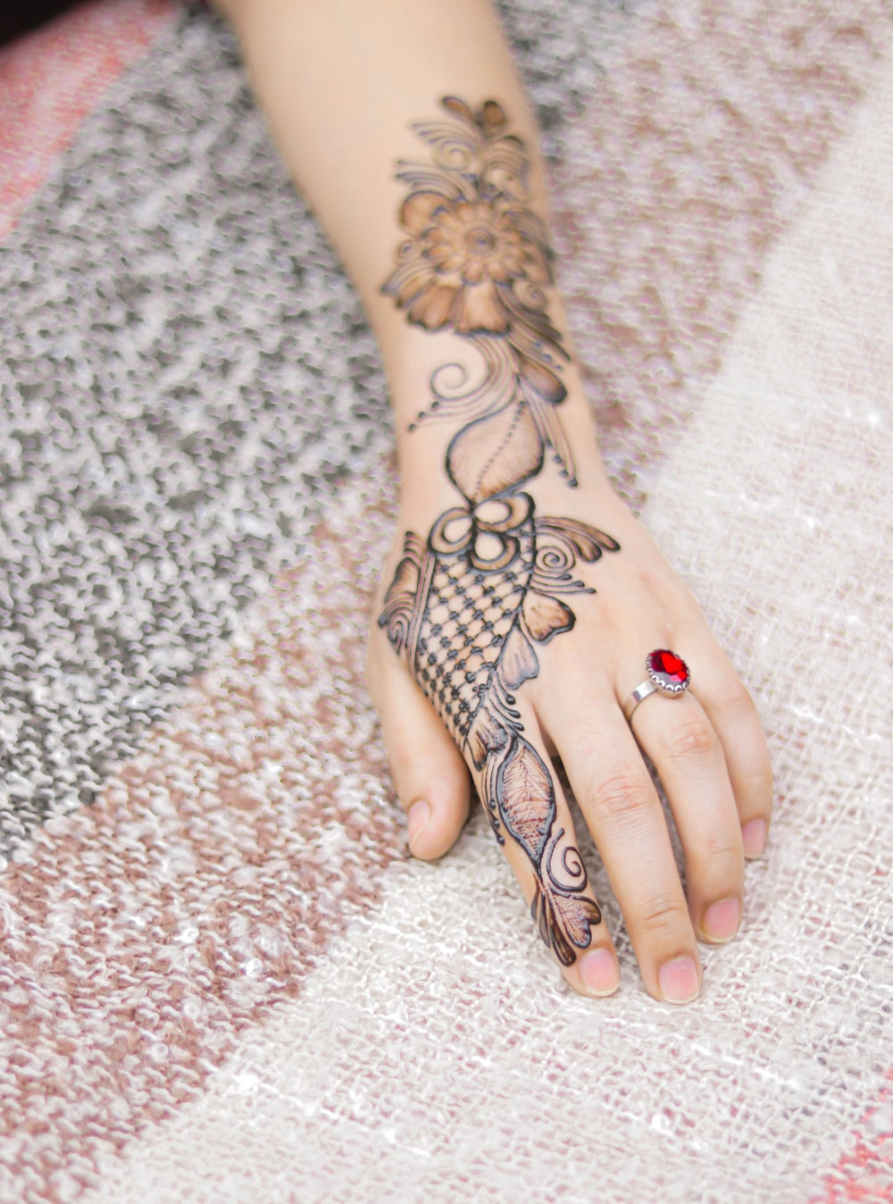 person with black and red flower tattoo on right hand