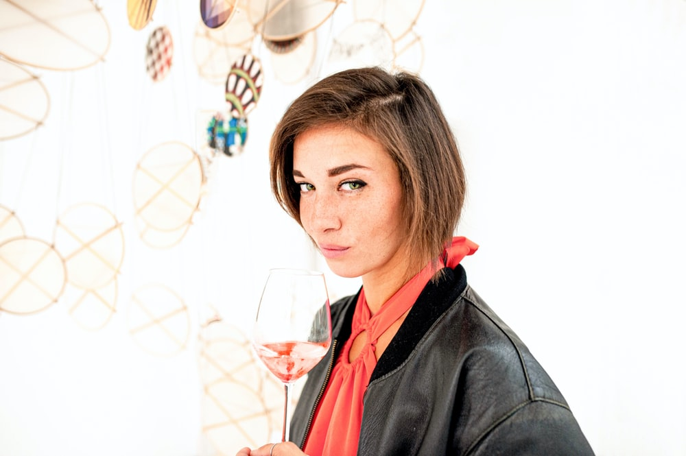 woman in black jacket holding wine glass