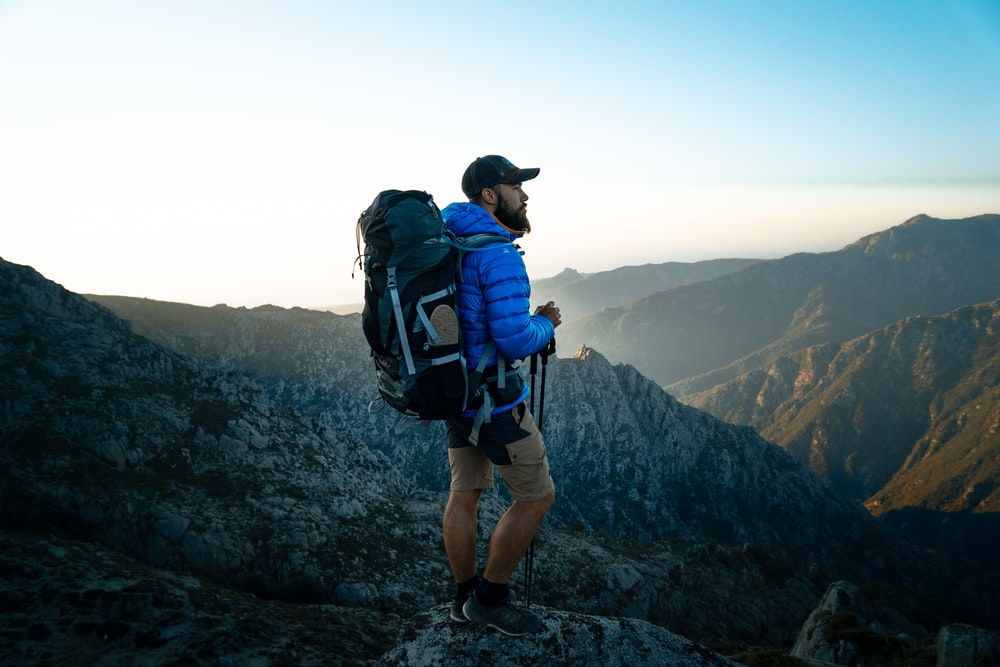 man in blue and black backpack standing on rock formation during daytime